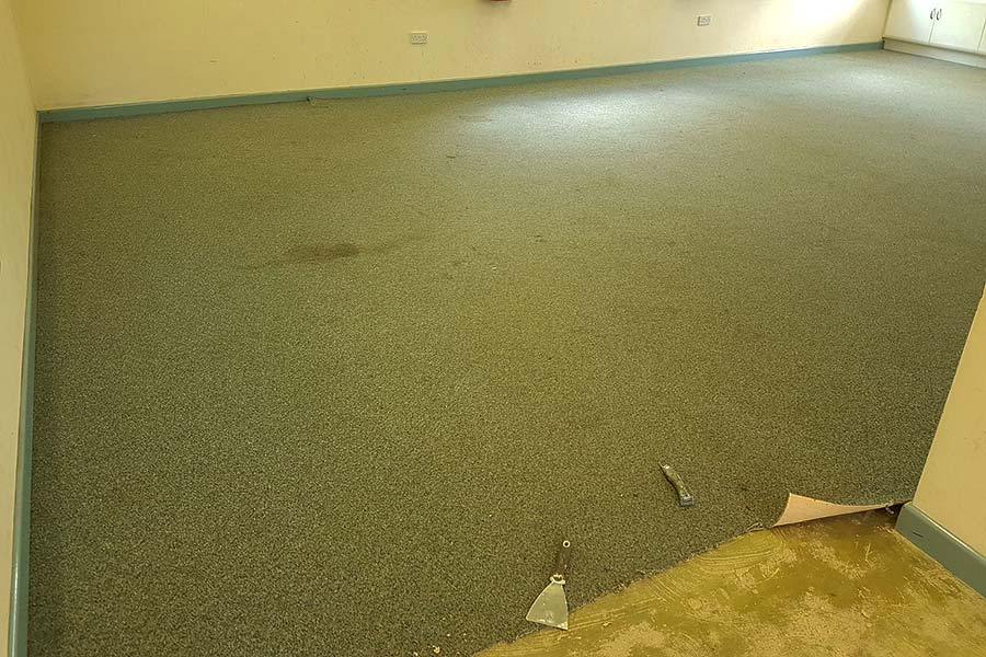 Removing the stained and worn carpet at Wareham village hall ready for new Karndean wood effect vinyl flooring