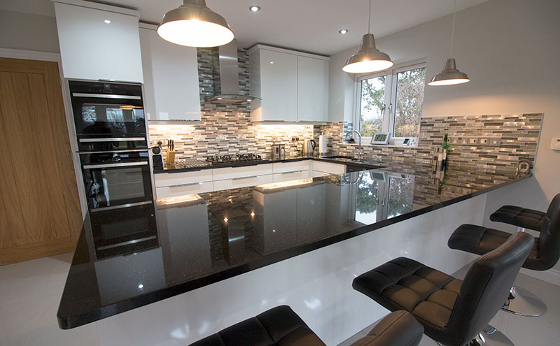 This modern kitchen near Swanage in Dorset features stone and glass mosaic splash backs with high gloss white porcelain floor tiles