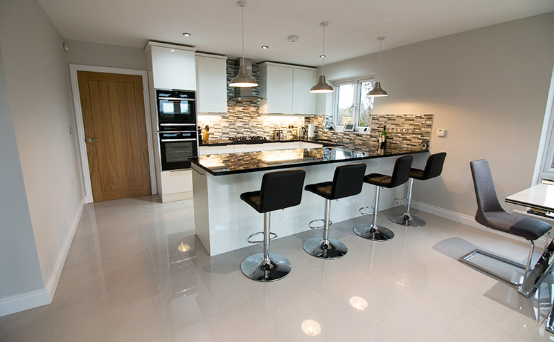 Large modern kitchen featuring high gloss floor tiles with stone and glass mosaics from UK Tiles Direct