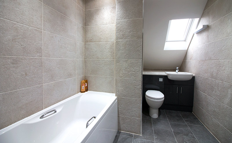 This modern family bathroom features Stoneway Black stone-effect porcelain floor tiles with contrasting Ivory wall tiles