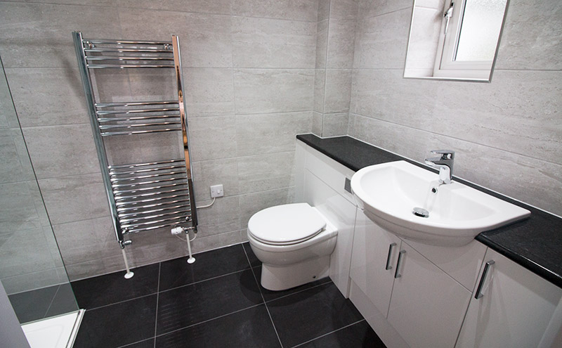 A luxury master ensuite bathroom by UK Tiles Direct featuring gloss black large format porcelain floor tiles with white stone effect wall tiles