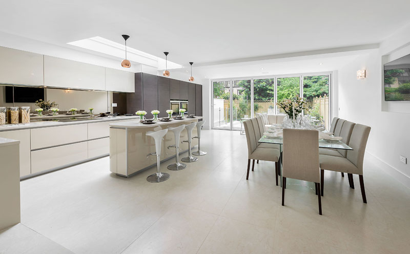 A large modern kitchen featuring oat meal coloured antibacterial porcelain floor tiles