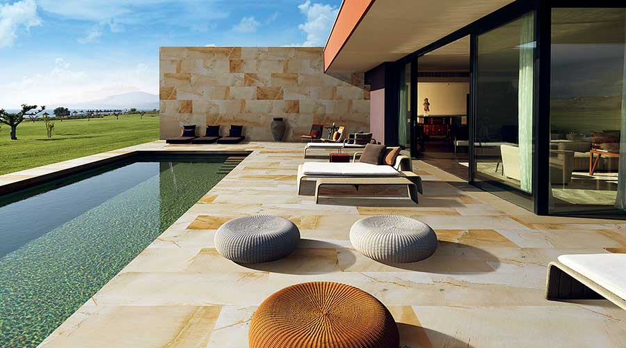 Sandstone effect thin porcelain tiles have been used for the patio and swimming pool of this stunning modern home
